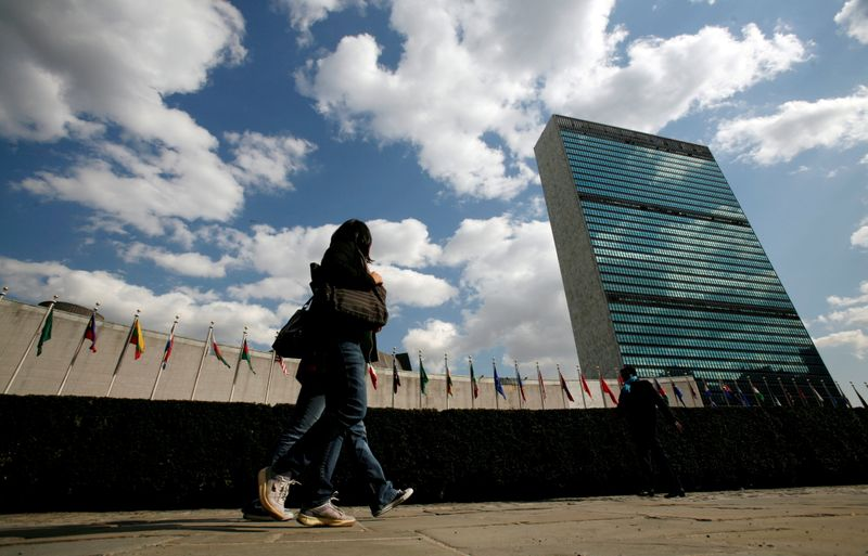 FILE PHOTO: Tourists pass United Nations Headquarters in New York
