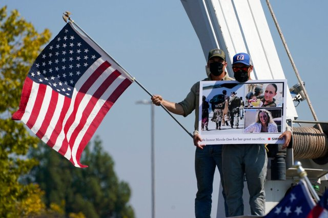 Sacramento Municipal Utility District employees fly a flag and display photos of Marine Corps. Sgt. Nicole L. Gee, as the hearse carrying her remains drives past on the way Mount Vernon Memorial Park in Fair Oaks, Calif., Thursday, Sept. 16, 2021. Gee, 23, was one of 13 U.S. service members who died in a bombing at Afghanistan's Kabul airport, last month.(AP Photo/Rich Pedroncelli)