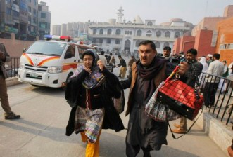 A Pakistani man and a woman rush to a hospital treating victims of a Taliban attack in Peshawar, Pakistan, Tuesday, Dec. 16, 2014. Taliban gunmen stormed a military-run school in the northwestern Pakistani city of Peshawar on Tuesday, killing and wounding scores, officials said, in the highest-profile militant attack to hit the troubled region in months.(AP Photo/Mohammad Sajjad)
