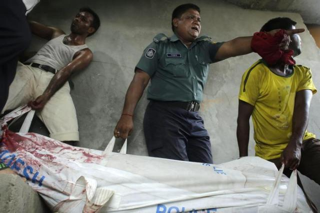 epa04875805 Police and others carry the body of a Ganajagaran Mancha activist and blogger Niloy Chakrabarty Neel to downstairs after he has been hacked to death by unknown assailants inside his house at Goran in Dhaka, Bangladesh 07 August 2015. According to the Offier in Charge Mustafizur Rahman, five assailants armed with machetes entered the flat in two groups after the Friday prayers and killed Niloy in his flat on the top floor of a four-storey building around 1:45pm local time. EPA/ABIR ABDULLAH
