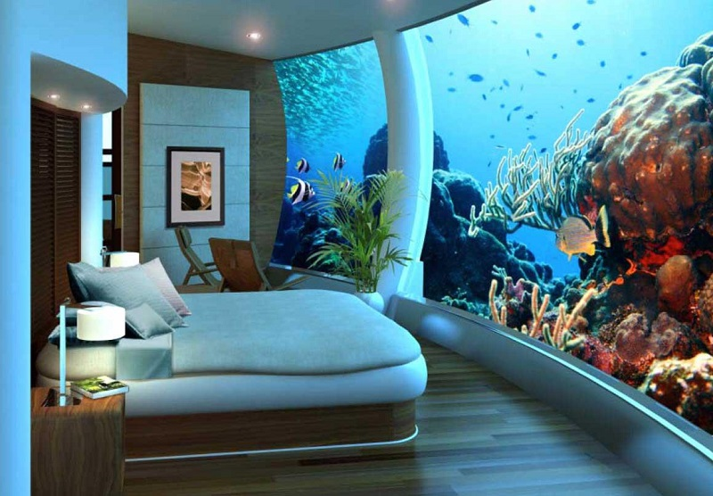 a bedroom with a a glass wall exposing a huge aquarium at the Poseidon Resort in Fidji