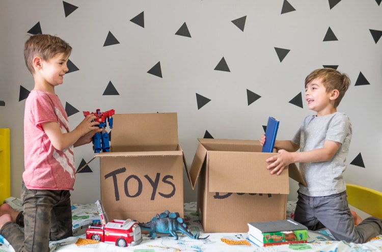 two boys packing up their toys in their bedroom