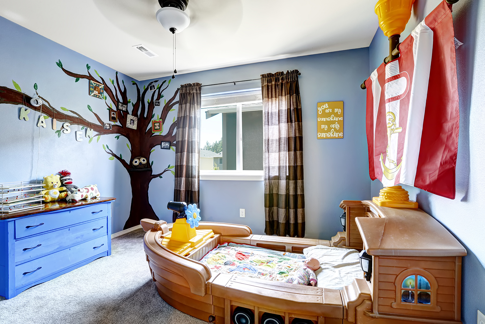 a mural on a tree on a kid's bedroom wall