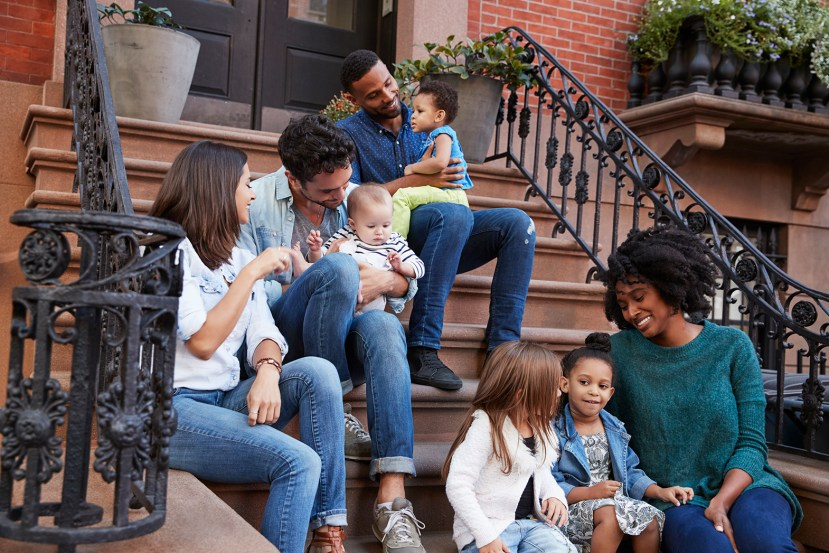 two families with young children sitting on stairs in front of an apartment