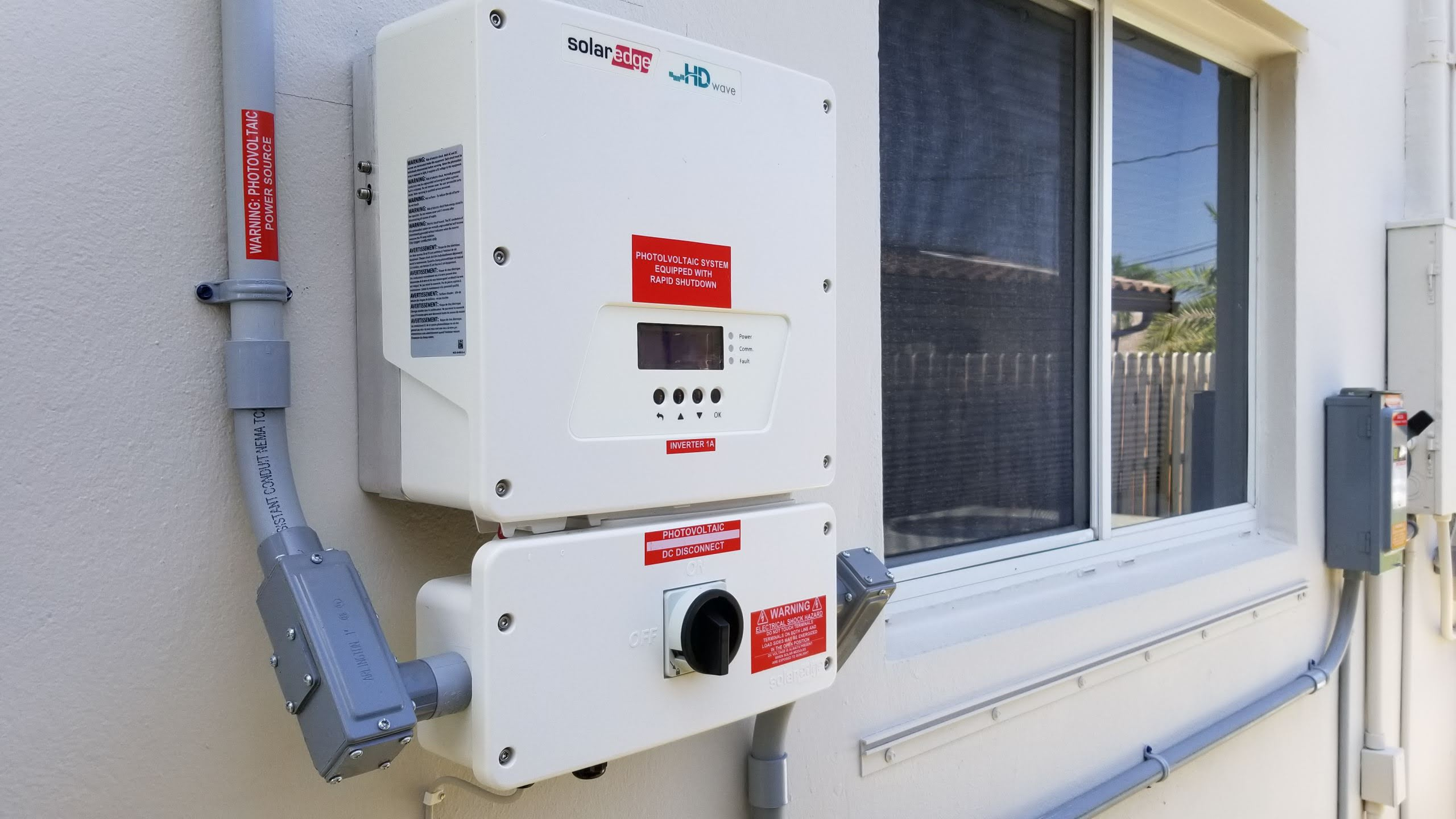 a transformer on the side of a house that connects the solar panels to the existing home power supply feed