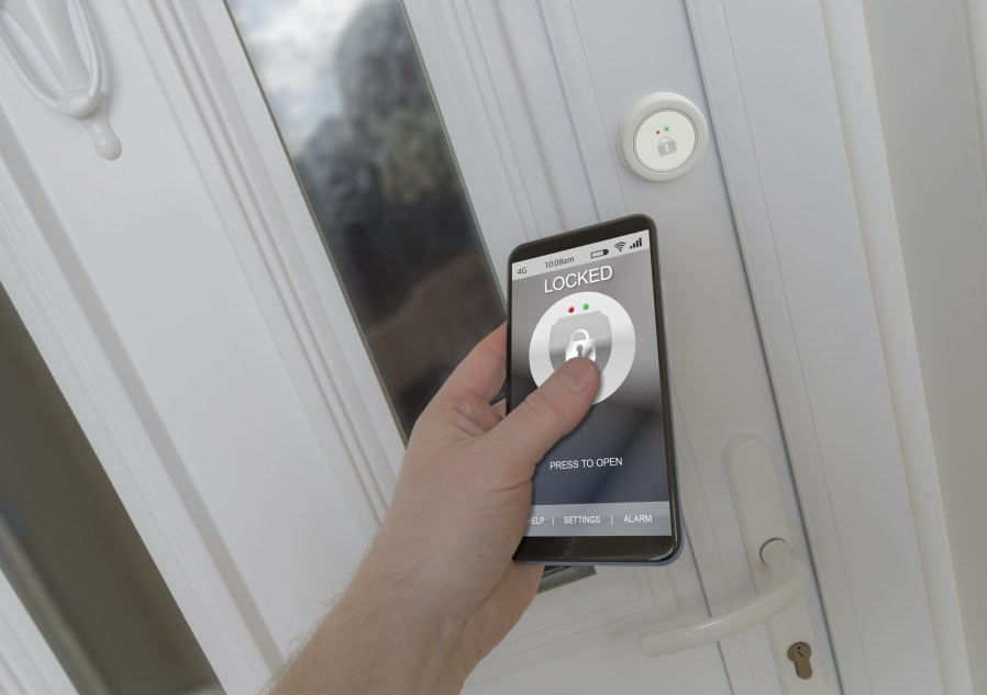 a person using a smartphone to open a smart lock on a front door