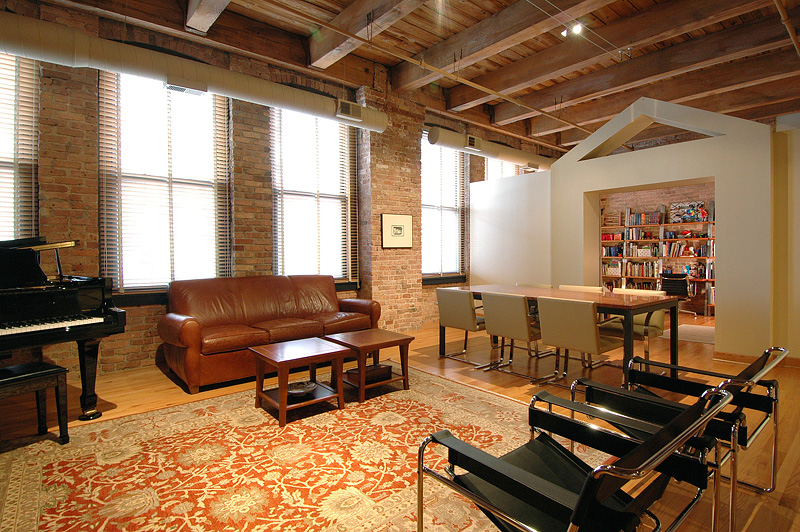 A warmly lit sitting area of an exposed brick loft
