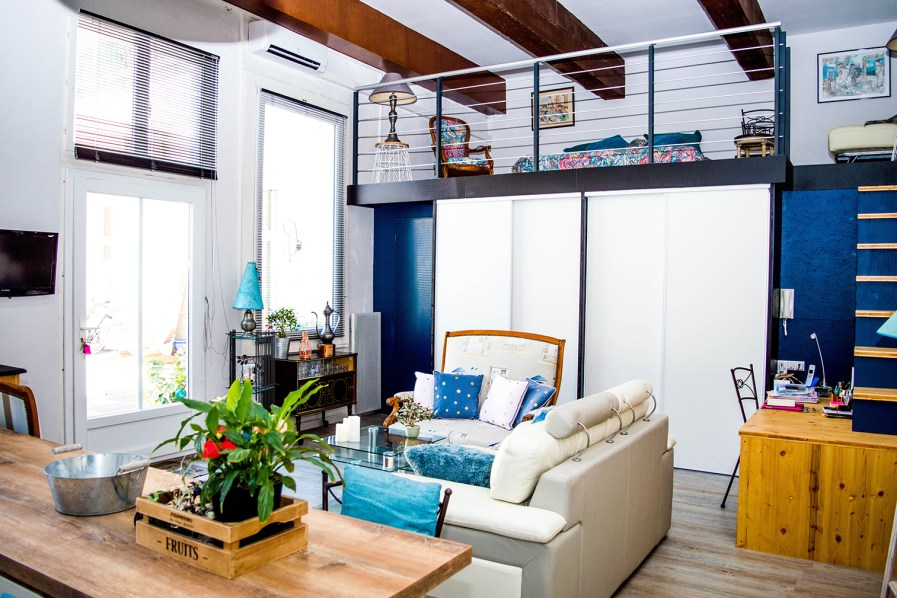 The living room area of a small, open-concept loft space with an upper level for a bed.