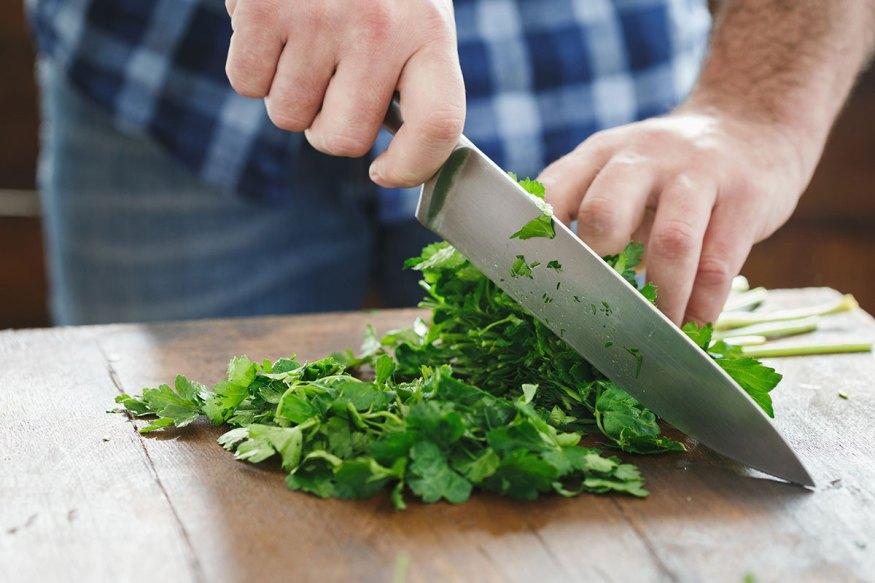 Someone is chopping leafy greens on a cutting board