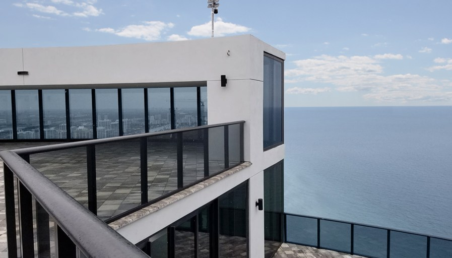 View towards penthouse from balcony with the sea behind and city reflecting in windows