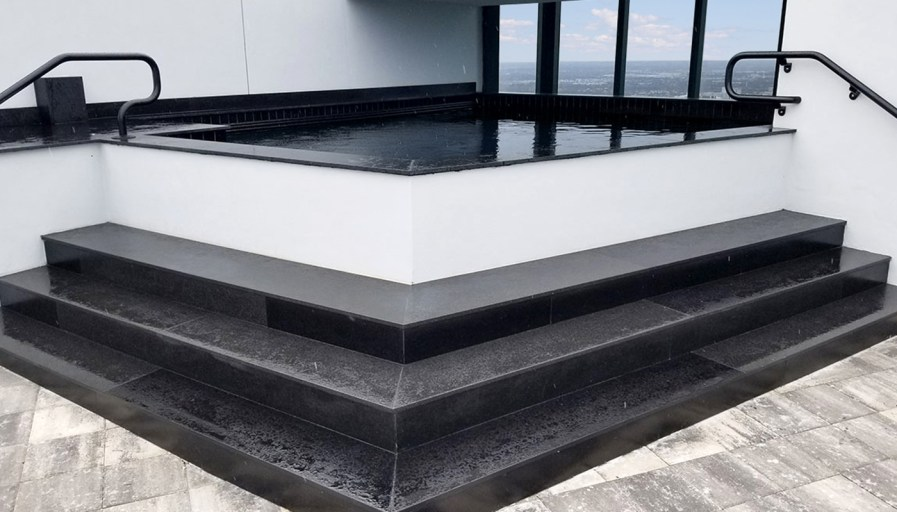 Hot tub on penthouse balcony with black marble steps
