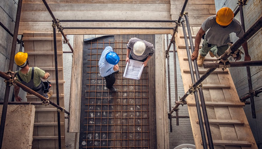 View looking down through scaffolding at construction crew working