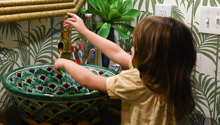 Little girl washing hands in peacock design ornamental sink in bathroom with palm frond wallpaper