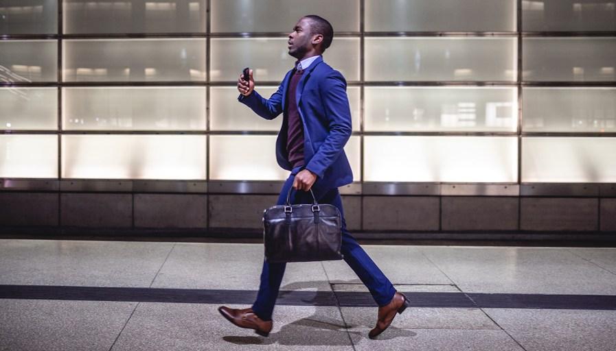 black man in a suit speed walking