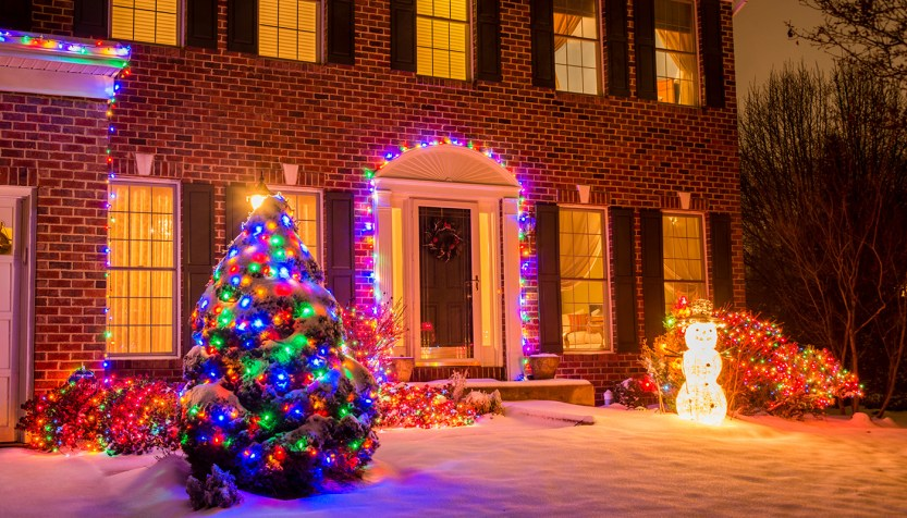 Red brick home with black shutters decorated with christmas lights