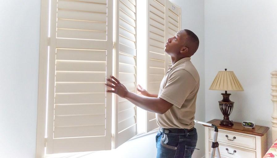 Man installing window coverings