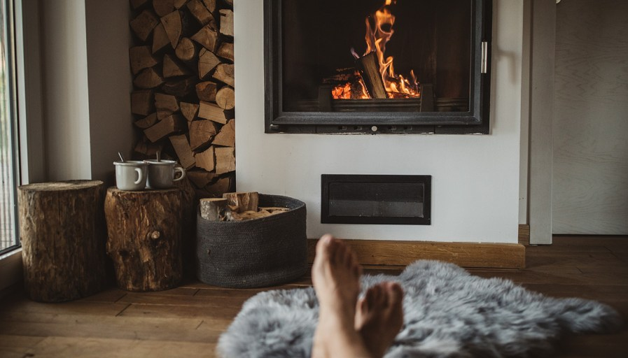 Man's feet being warmed by a fireplace