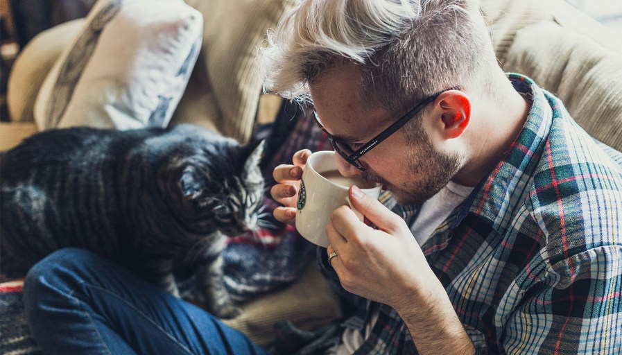 A man sipping coffee with a cat beside him
