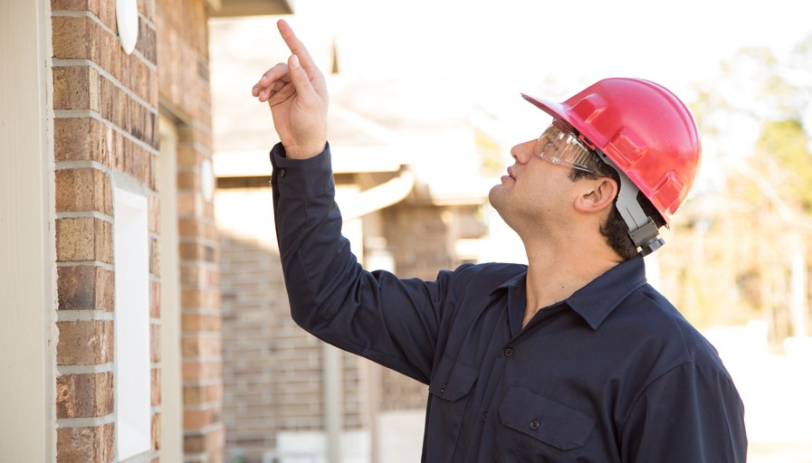Man wearing hard hat and pointing to something on exterior of home