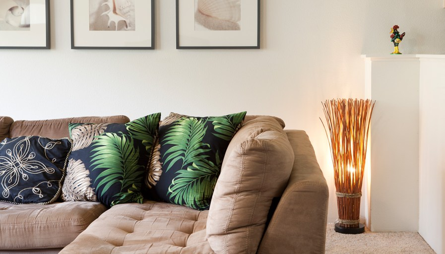 Beige couch with tropical pillows