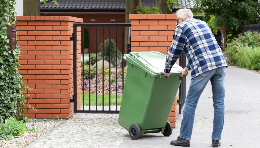 A man taking out his garbage.