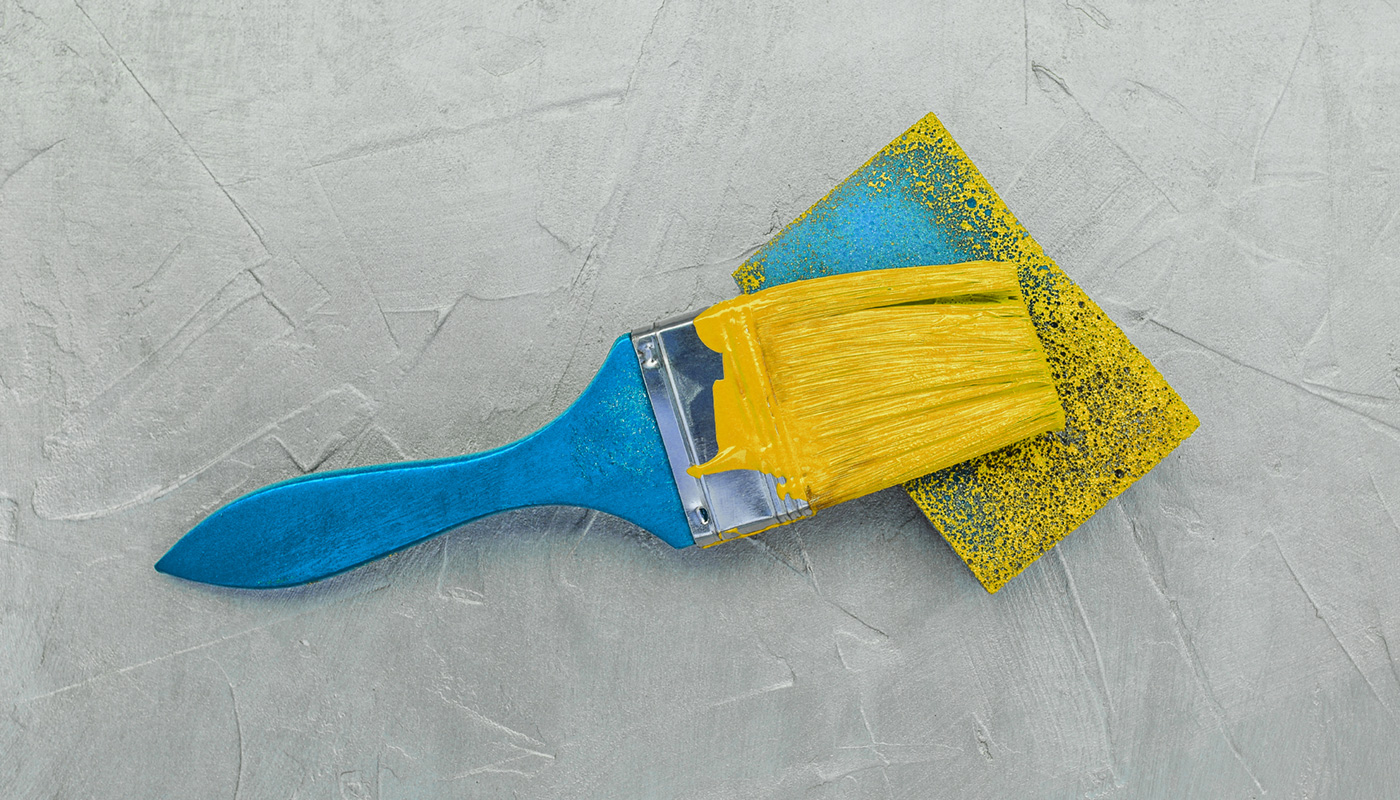 a blue paint brush with yellow paint laying on a sponge