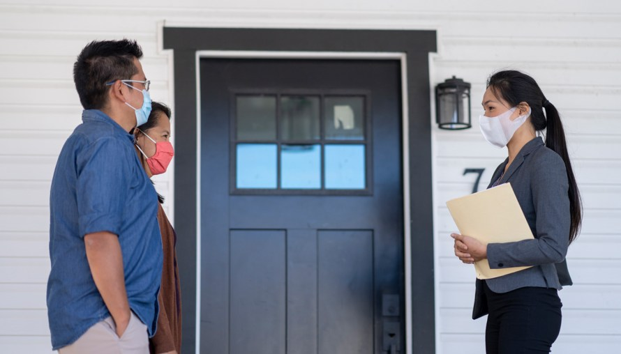 Couple meeting woth broker outside of new home