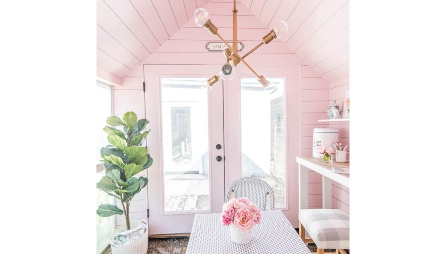 inside a shed that has been turned into a backyard oasis with pink walls, a table, and chairs