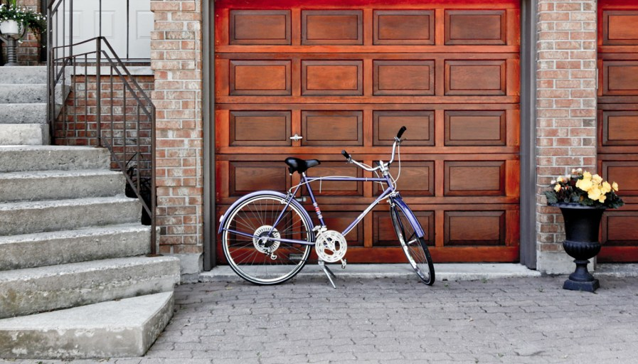 A bicycle sitting in front of a wooden garage with an interlocking driveway