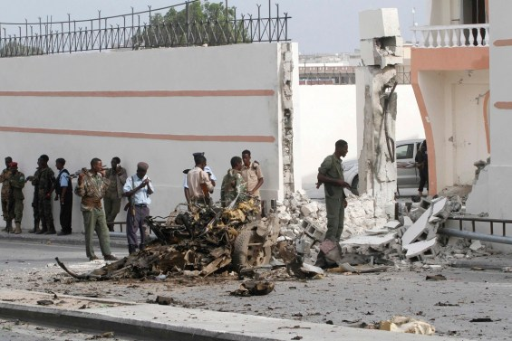 Somali government forces assess the scene of a suicide car explosion in front of the SYL hotel in the capital Mogadishu
