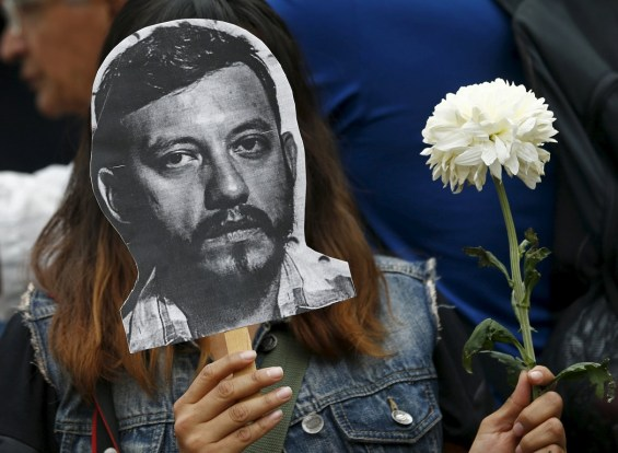 An activist holds up a picture of photojournalist Espinosa during a protest against his murder at the Angel of Independence monument in Mexico City
