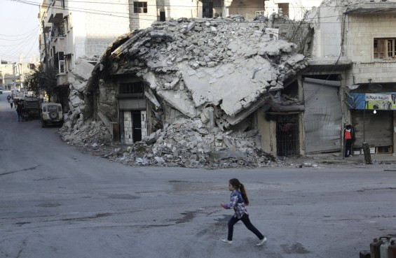 A girl runs past damaged buildings in the rebel-controlled area of Maaret al-Numan town in Idlib province, Syria