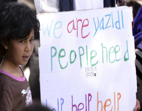 A little girl stands next to a placard at the Moria refugee camp, on the Greek island of Lesbos, prior to the arrival of Pope Francis