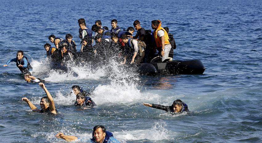 Afghan refugees struggle to swim ashore after their dinghy with a broken engine drifted out of control off the Greek island of Lesbos