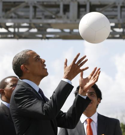 U.S. President Obama plays with a soccer ball during a demonstration at the Ubungo Power Plant in Dar es Salaam