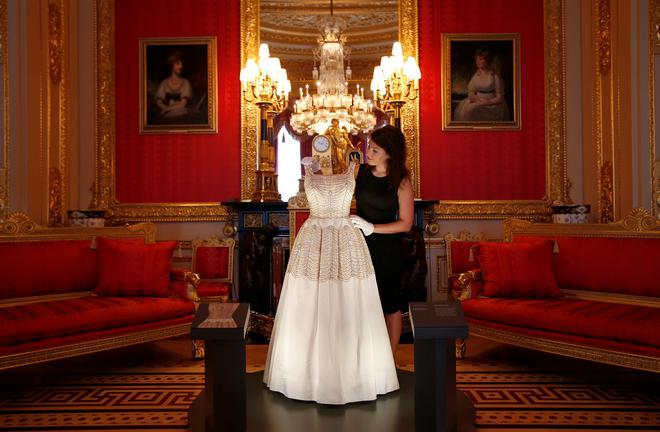 A member of staff of the Royal Collection poses with a dress worn by Britain's Queen Elizabeth, at Windsor Castle in Windsor