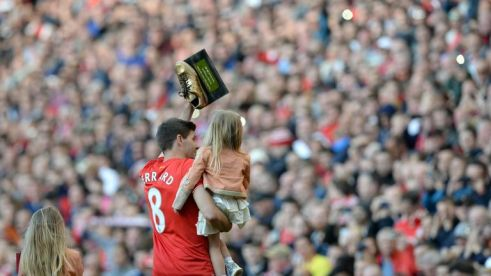 Steven Gerrard holding his daughter waves to the fans following his final home game for Liverpool