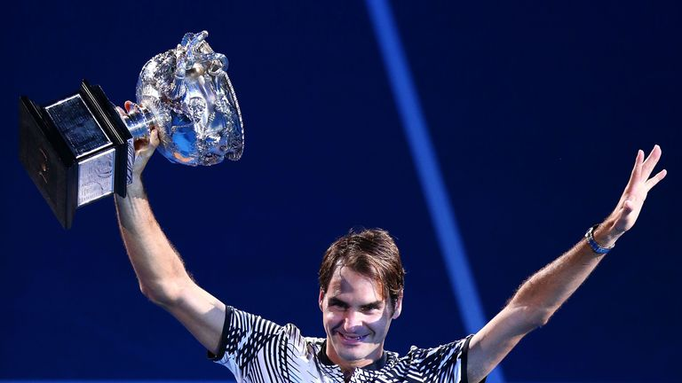 Roger Federer holds the Australian Open trophy aloft after beating old rival Rafael Nadal in a five-set thriller