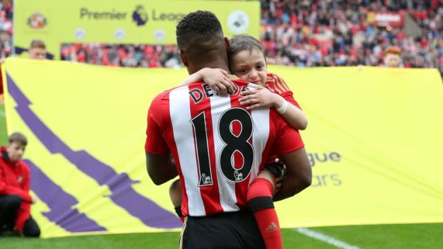 Bradley Lowery is held by Sunderland's Jermain Defoe