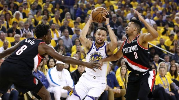 Stephen Curry drives at CJ McCollum in Game 1 of the Western Conference Finals