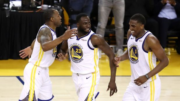 Draymond Green #23 of the Golden State Warriors celebrates with Andre Iguodala #9 and Kevon Looney #5 during the second half against the Portland Trail Blazers in game one of the NBA Western Conference Finals at ORACLE Arena on May 14, 2019 in Oakland, California.