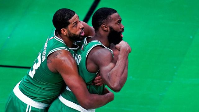 AP - Boston Celtics guard Jaylen Brown, right, flexes after scoring a basket, while being embraced by Tristan Thompson