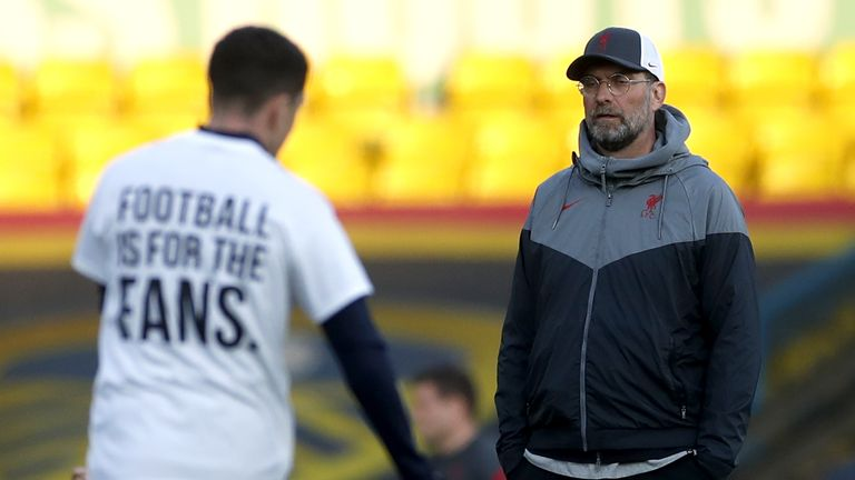 Liverpool manager Jurgen Klopp looks on as a Leeds United player warms up on the pitch wearing a shirt opposing the new European Super League