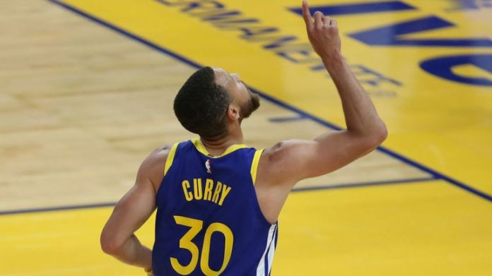 Golden State Warriors' Stephen Curry points to the sky after scoring against the Oklahoma City Thunder during the first half of an NBA basketball game in San Francisco, Saturday, May 8, 2021.