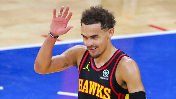 Atlanta Hawks guard Trae Young waves to booing Philadelphia 76ers fans after winning Game 7 of their NBA Eastern Conference semifinal game to advance, Sunday, June 20, 2021, in Philadelphia. (Curtis Compton/Atlanta Journal-Constitution via AP)