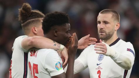 England's Kalvin Phillips and Luke Shaw comfort teammate Bukayo Saka after he failed to score a penalty during a penalty shootout after extra time during of the Euro 2020 soccer championship final match between England and Italy at Wembley