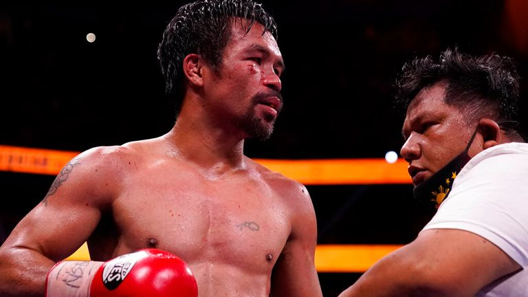 Manny Pacquiao, of the Philippines, waits in the ring with a trainer after losing his fight to Yordenis Ugas, of Cuba, in a welterweight championship boxing match Saturday, Aug. 21, 2021, in Las Vegas. (AP Photo/John Locher)