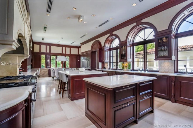 Italian style kitchen and hardwood, with double islands and integrated dining room with benches.