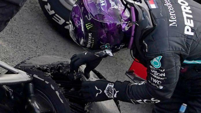 Lewis Hamilton examina la rueda desllantada con la que pudo cruzar la...