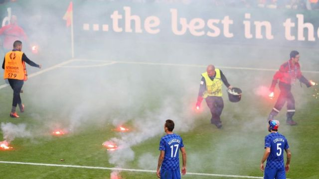 Workers clear the field after crowd disorder in the match between Croatia and Czech Republic